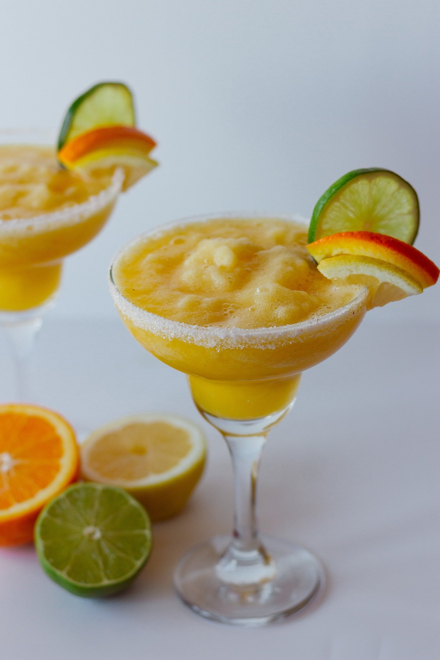 2 margarita glasses containing fresh citrus margarita on a light background