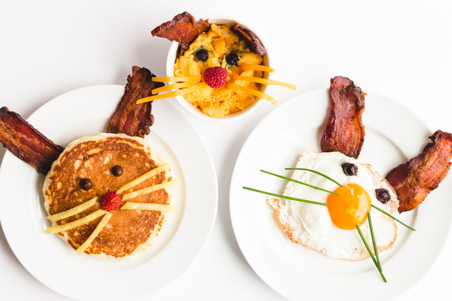 3 plates containing bacon and eggs or pancake breakfast that looks like an Easter Bunny. There is a pancake bunny, scrambled eggs bunny and fried egg bunny.