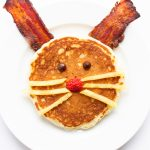 Bacon and Pancake breakfast shaped like an Easter bunny on a white plate