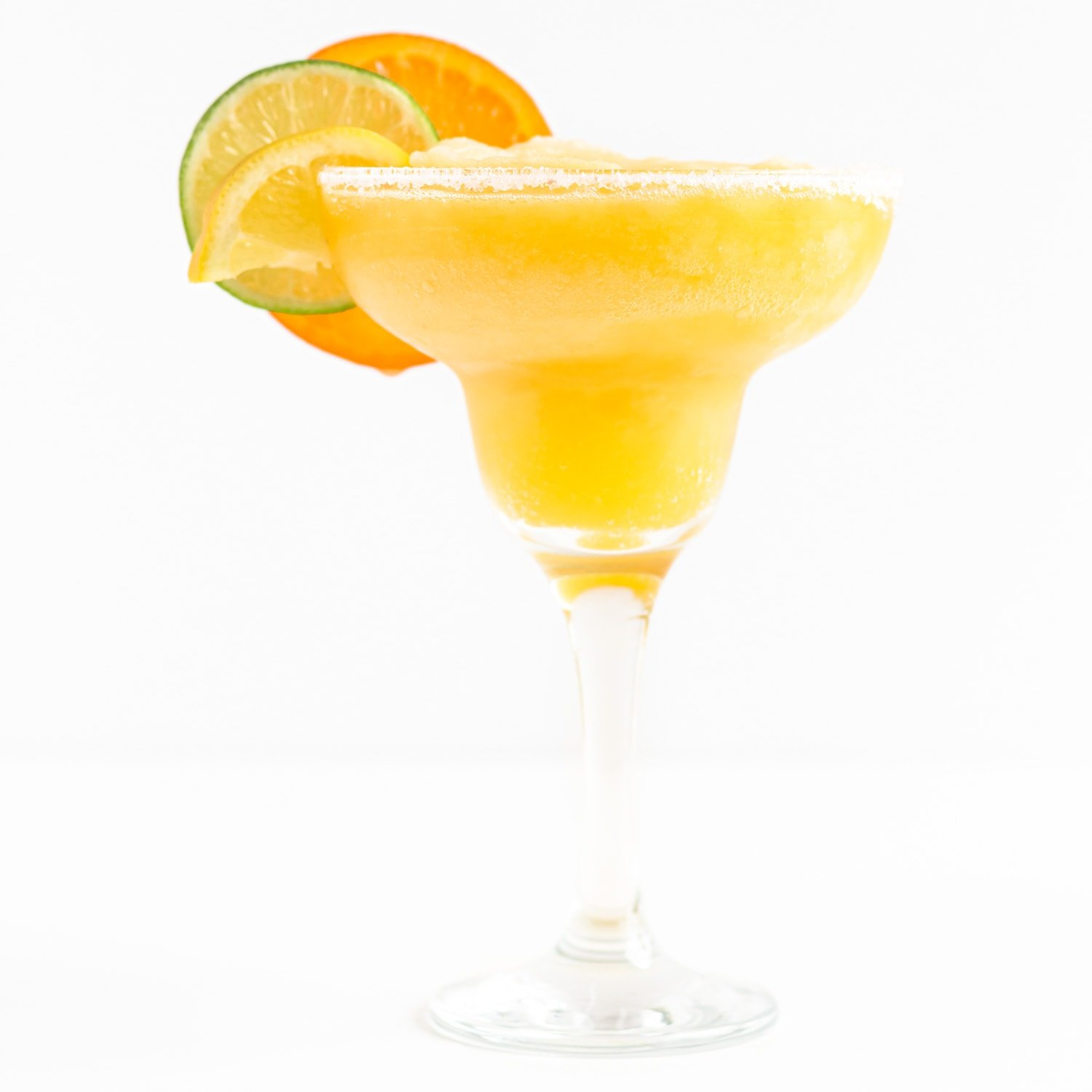 Single frozen citrus margarita garnished with orange, lemon and lime slices on a white background.