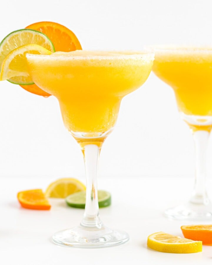 Two margarita glasses filled with frozen citrus margarita and garnished with orange, lemon and lime slices.