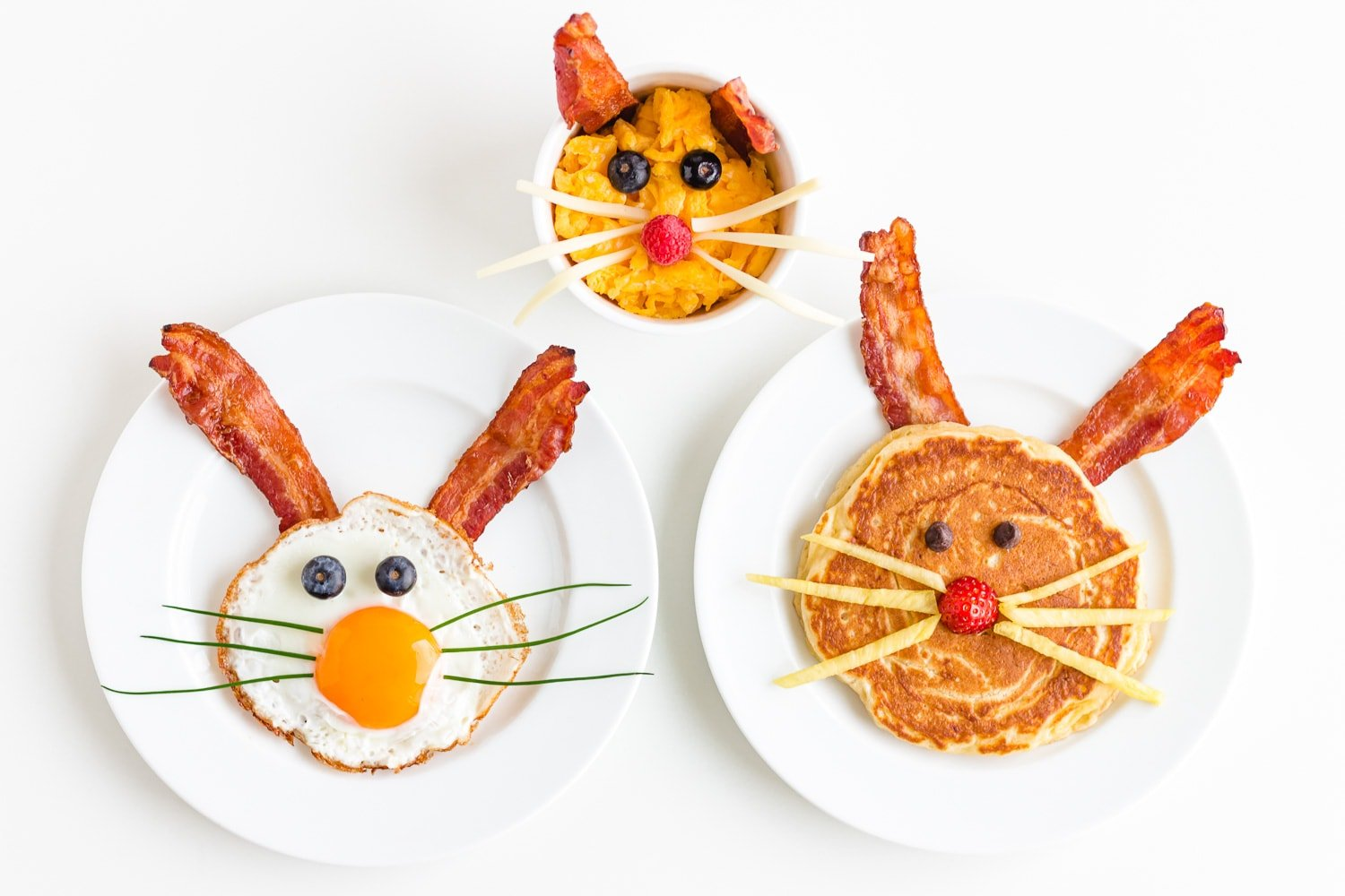 Three versions of an Easter Bunny themed breakfast including a bunny pancake, bunny scrambled eggs and a fried egg bunny.