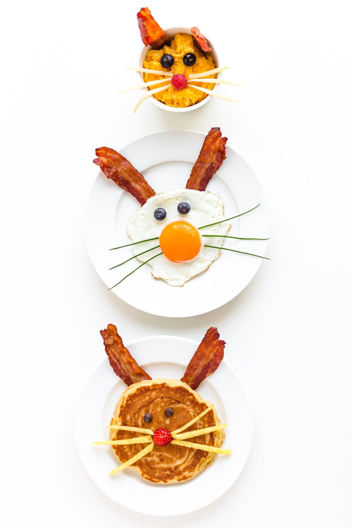 Three versions of an Easter Bunny themed breakfast displayed on a white background.  Easter Bunny pancake, fried egg bunny and scrambled egg bunny.
