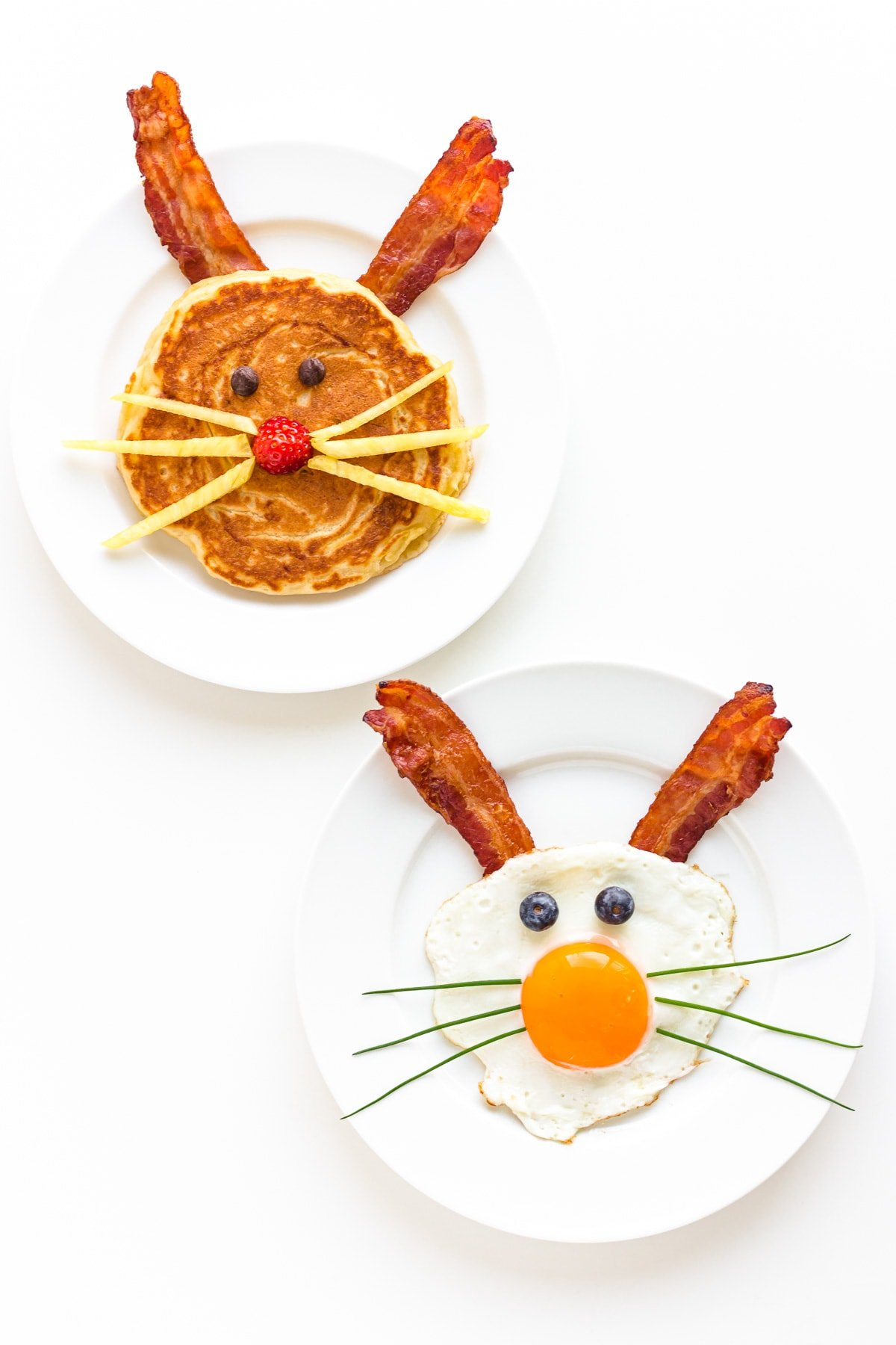 A bunny pancake with bacon ears and a sunny side up fried egg and bacon bunny on separate white plates.