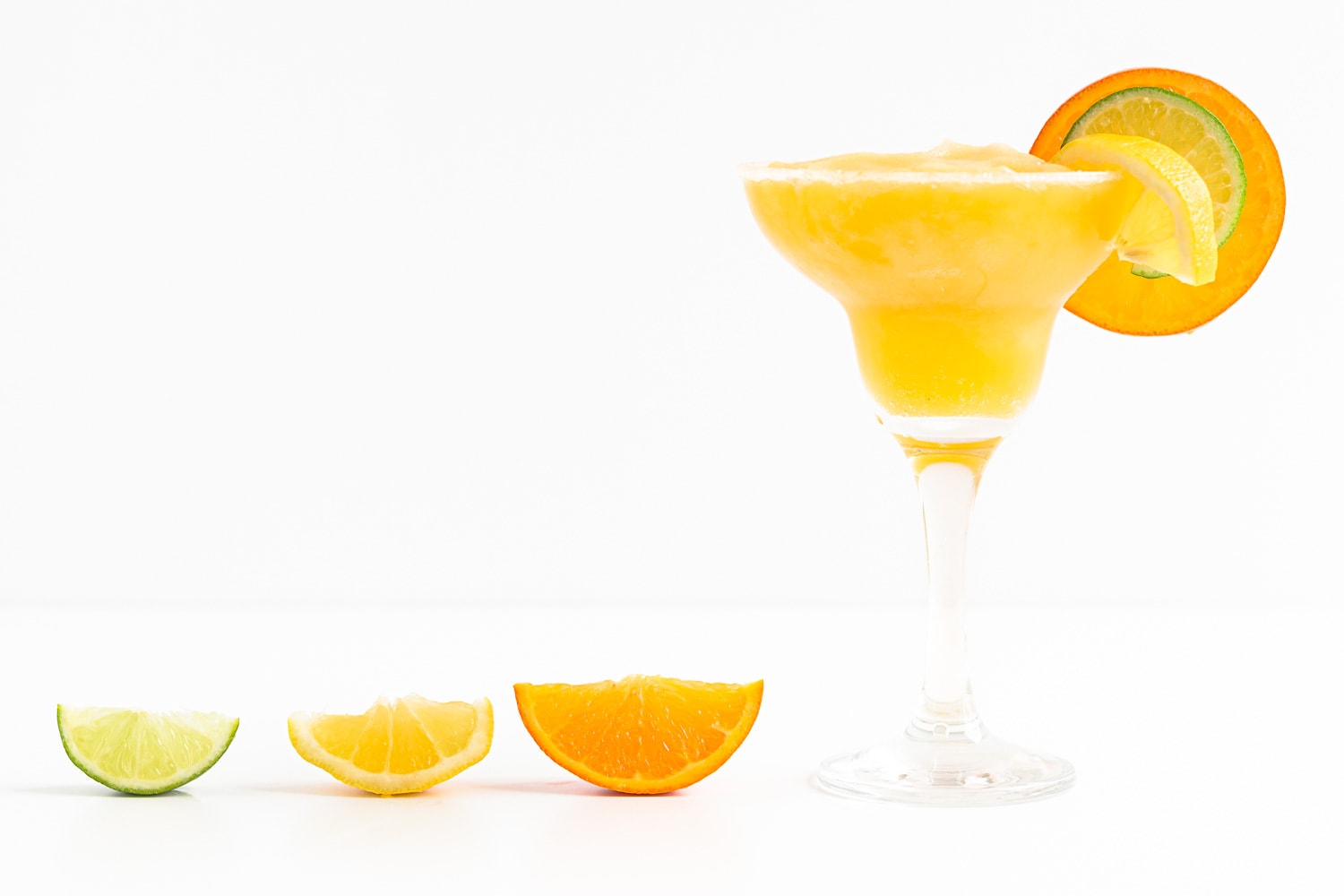 A wedge of lime, lemon and orange next to a glass of frozen citrus margarita.