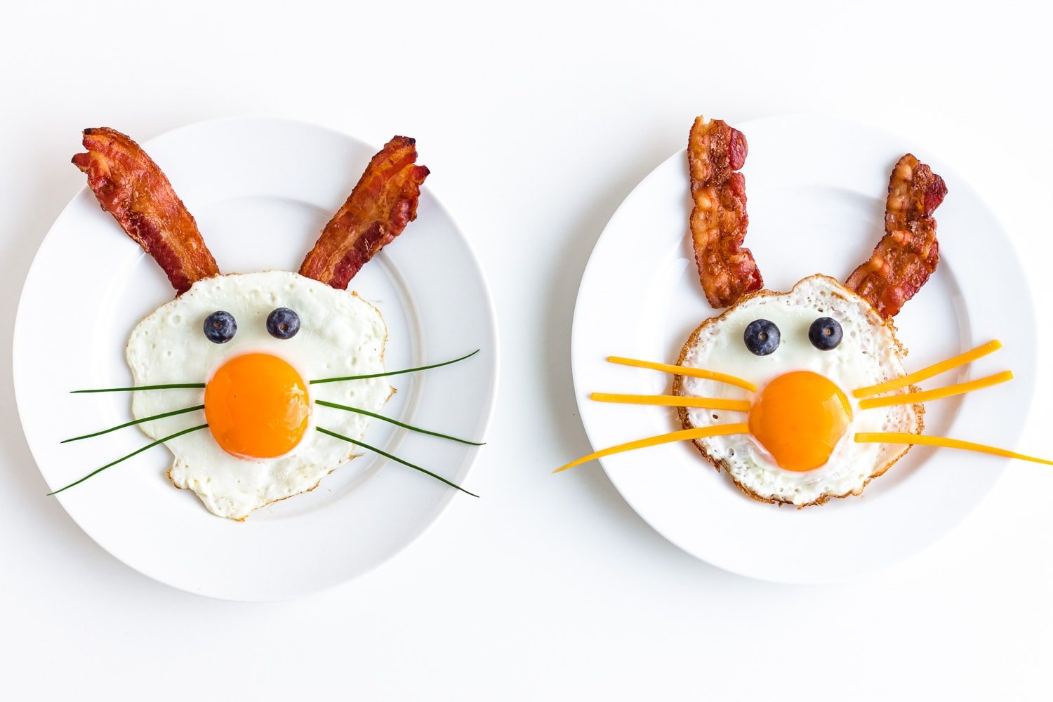 Two fried egg bunnies on white plates with bacon for ears, blueberries for eyes and chives or cheese for whiskers.
