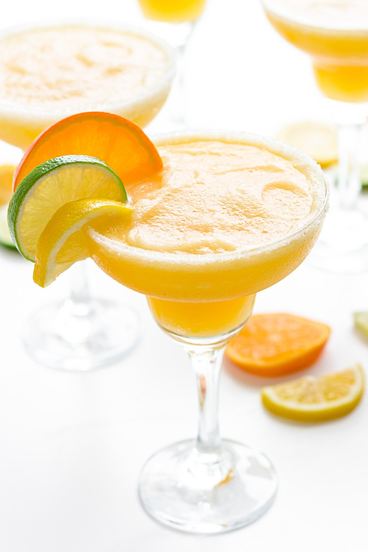 Frozen citrus margaritas garnished with slice of orange, lemon and lime.