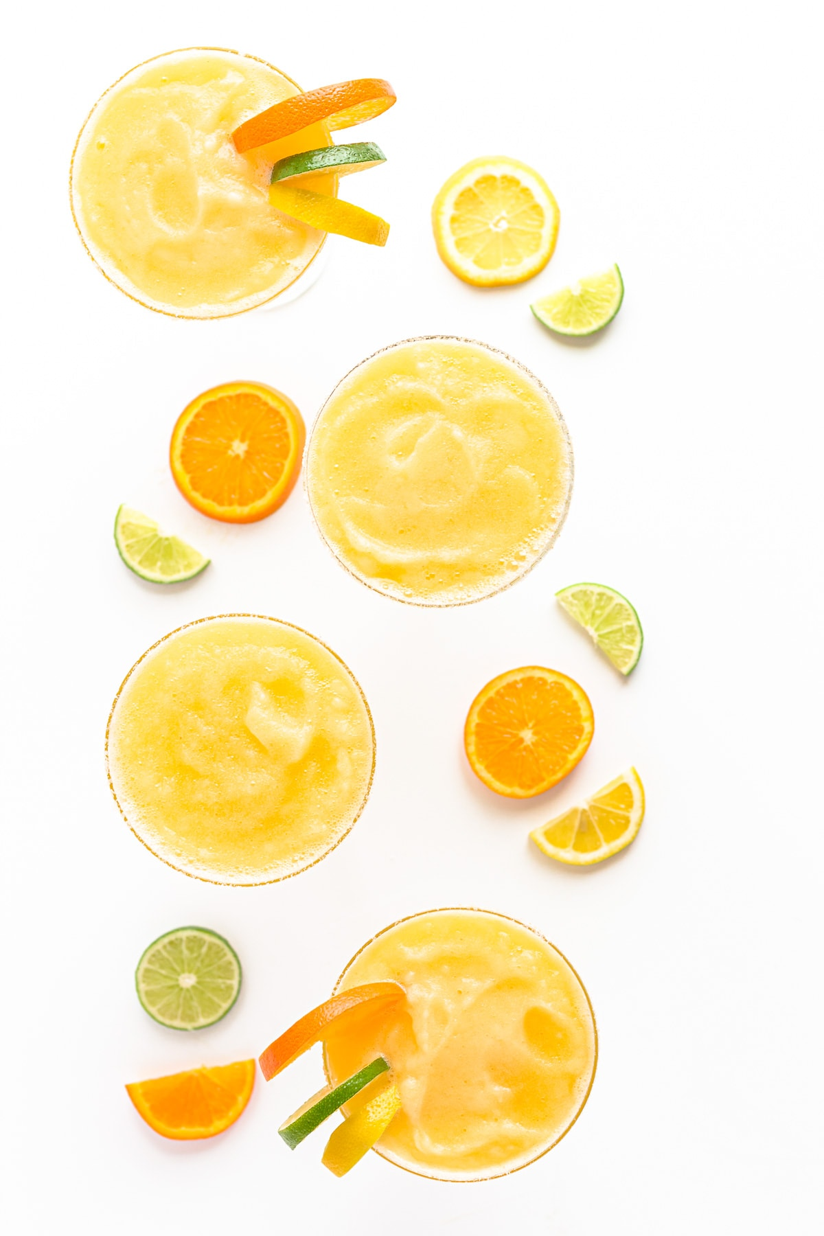 Overhead view of four citrus margaritas garnished with orange, lemon and lime slices.