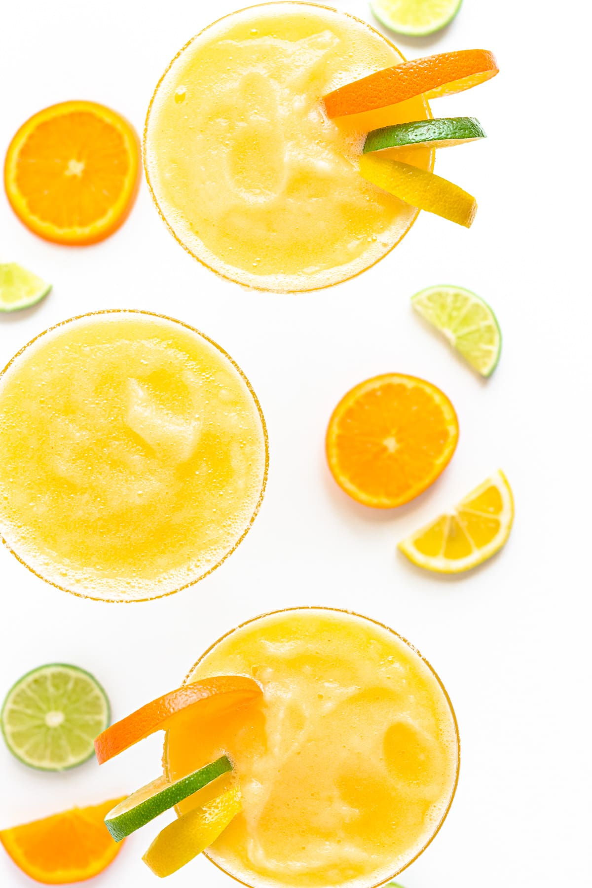Overhead view of three frozen margaritas garnished with orange, lemon and lime slices.