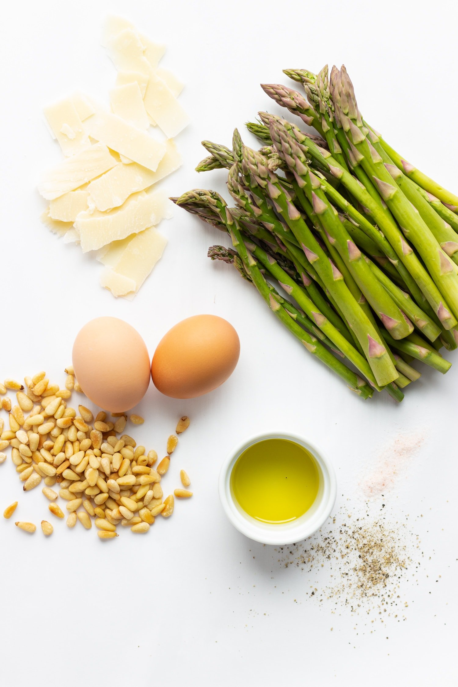 asparagus, parmesan shavings, eggs, toasted pine nuts, small white bowl of olive oil, himalayan salt and freshly ground pepper on a white surface