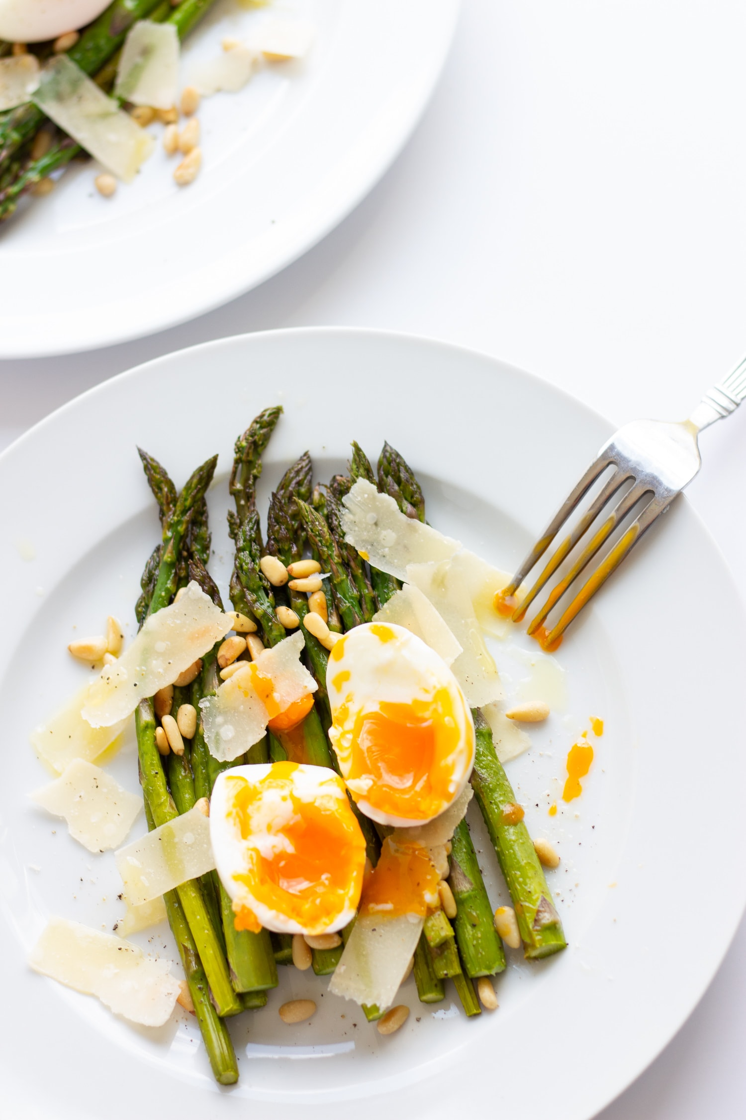 roasted asparagus on a white plate topped with soft boiled egg, parmesan shavings and toasted pine nuts with fork on the side