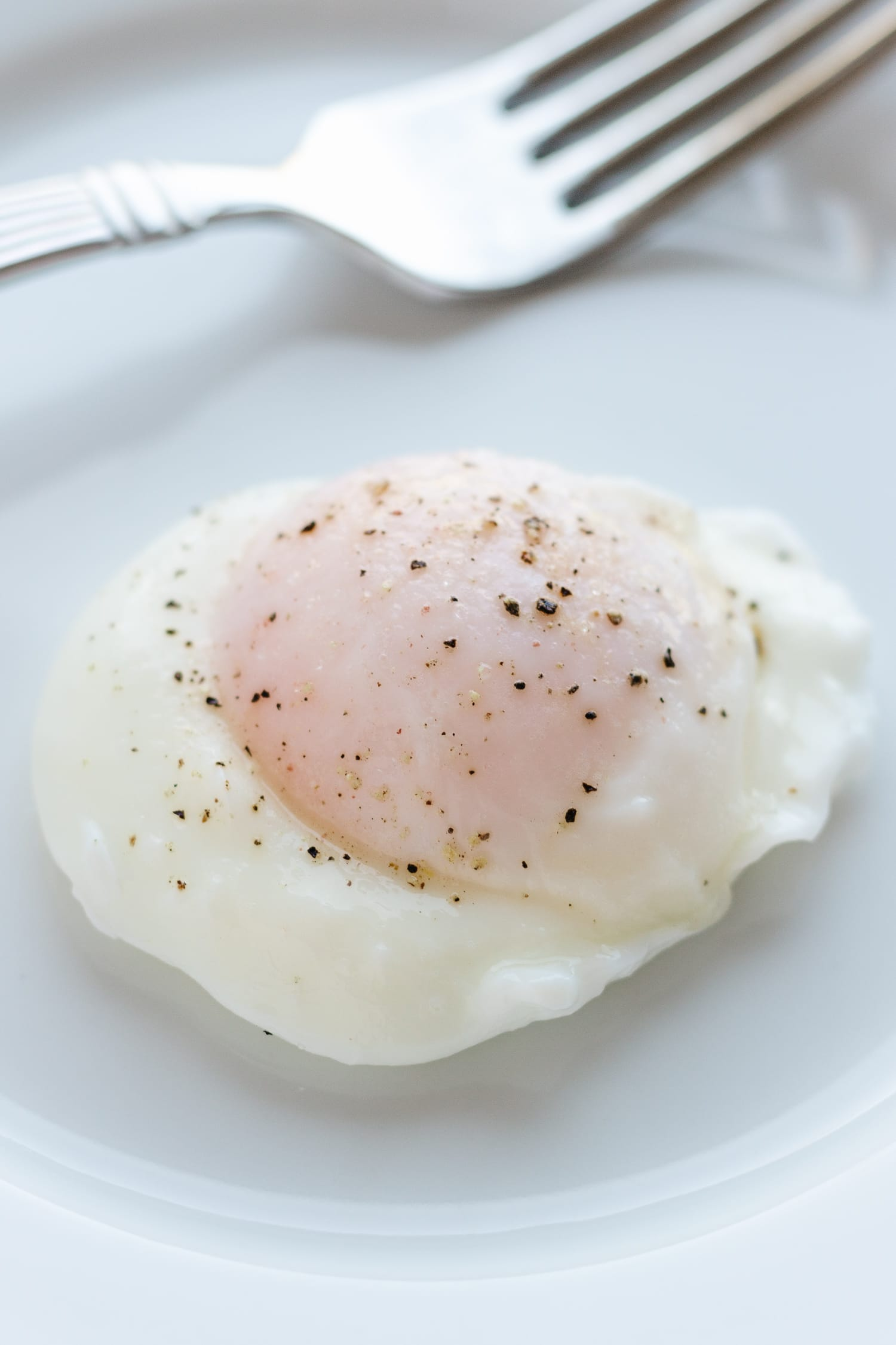 poached egg with a fork on a white plate