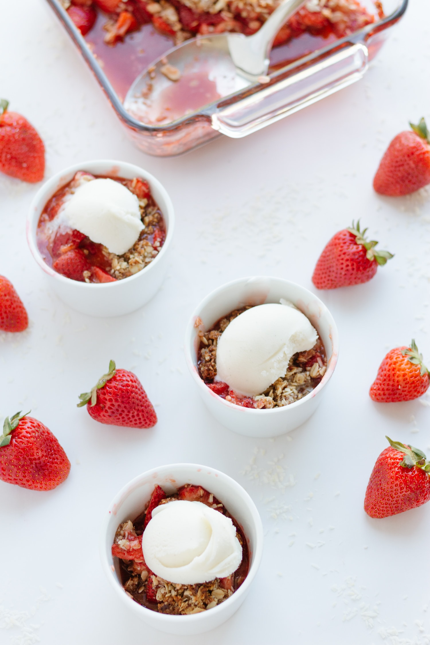 Three ramekins of strawberry coconut crisp topped with ice cream  with baking dish in background and strawberries scattered on white surface.