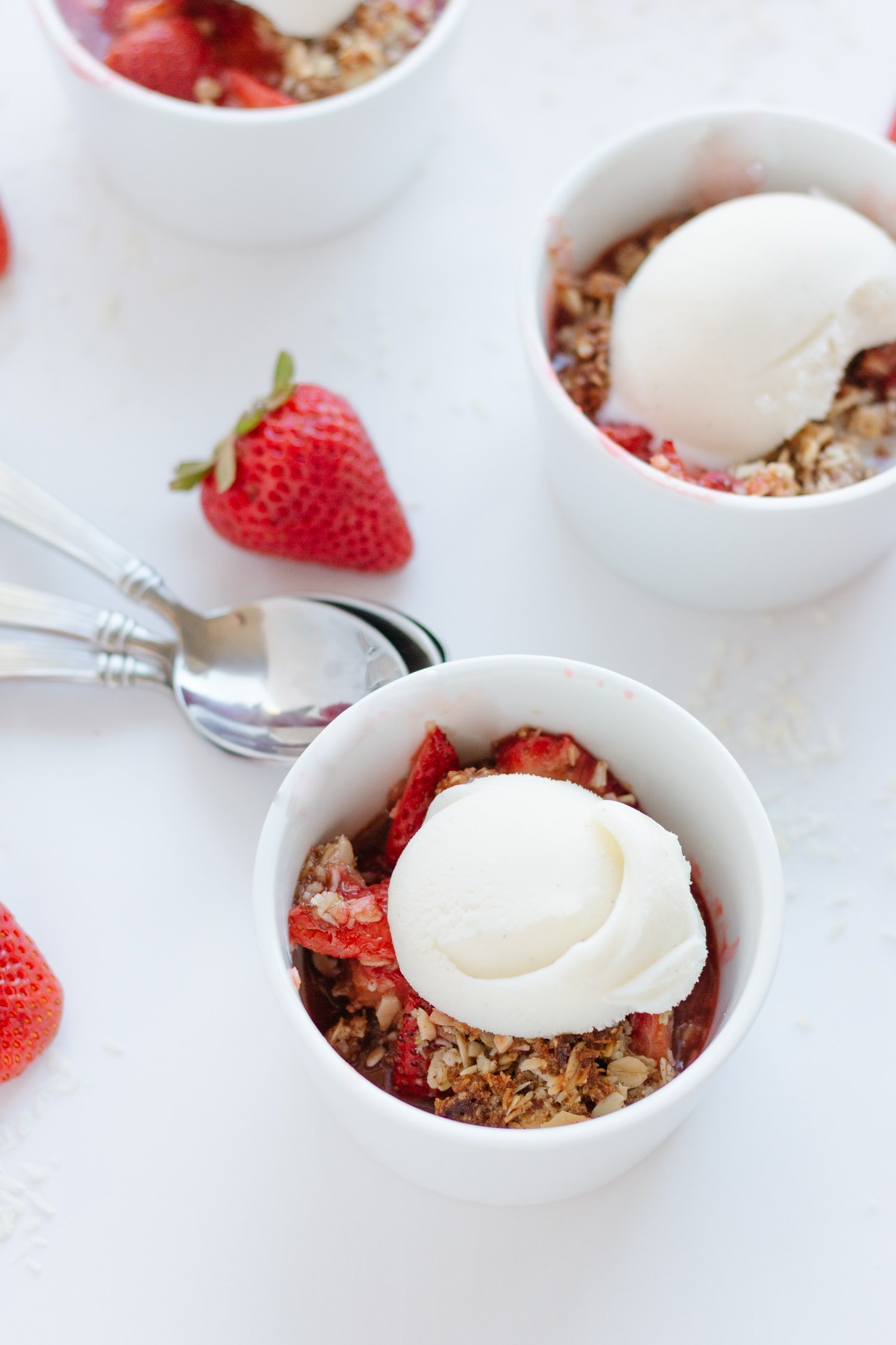 Strawberry Coconut Crisp in three white ramekins topped with a scoop of vanilla ice cream