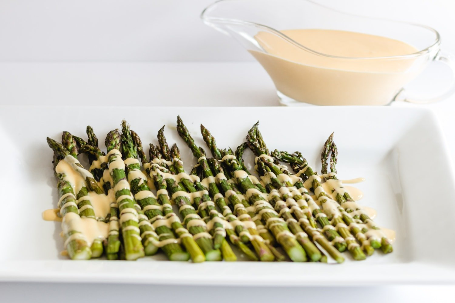 aspargus on a white platter with hollandaise sauce