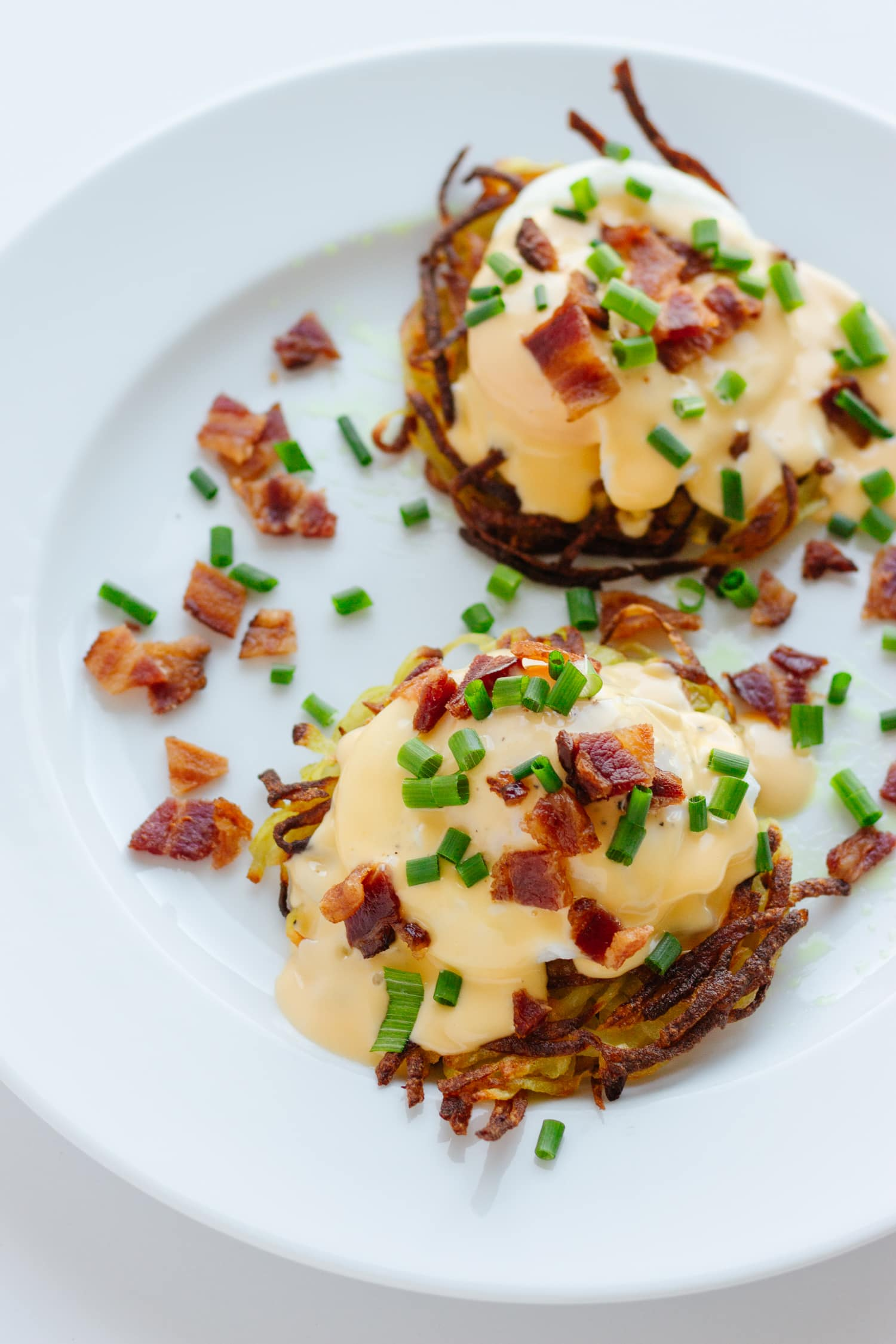 Two rosti eggs benedict on a white plate with bacon bits and chopped chives scattered over