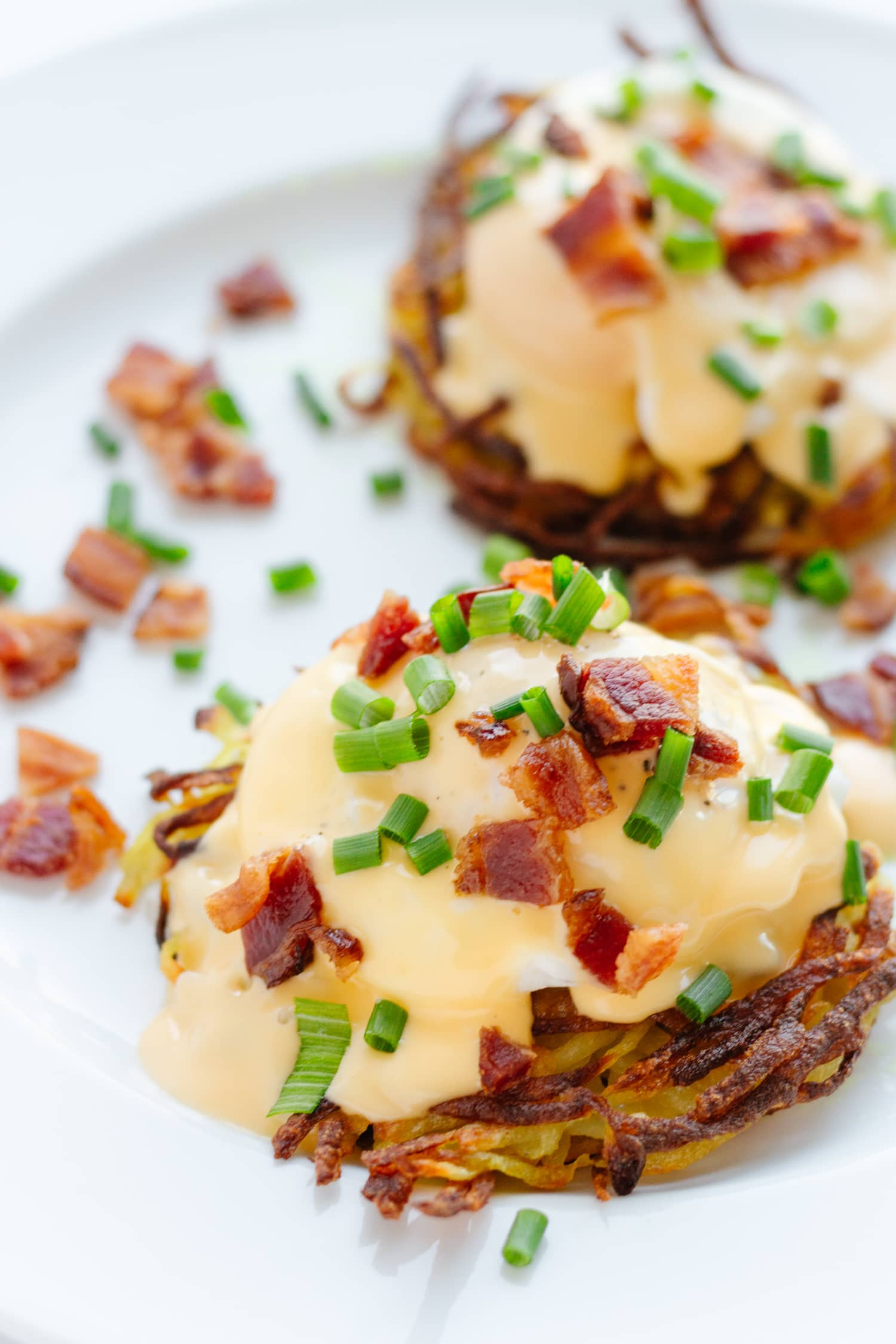 rosti with poached egg, hollandaise sauce, bacon bits and chives on a white plate