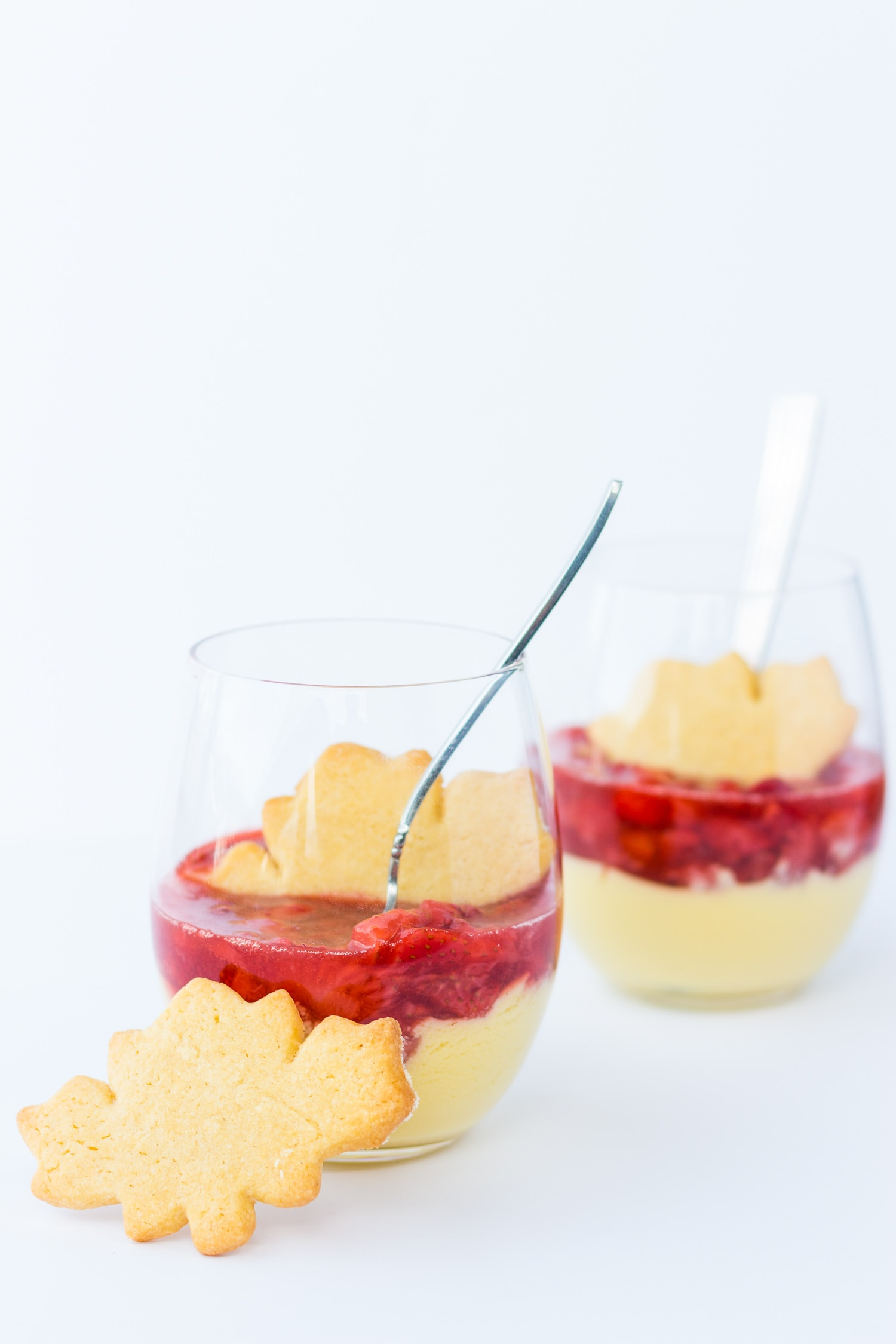 Two glasses of maple custard with strawberry compote with maple leaf shaped sugar cookies.