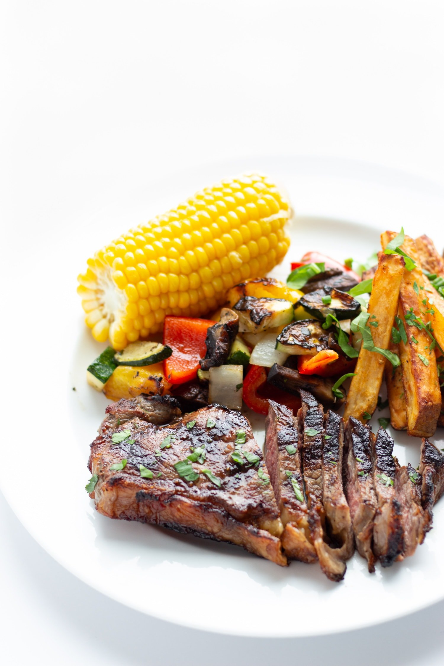 Grilled steak dinner on a white plate containing steak, corn on the cob, grilled mixed vegetables and roasted potatoes