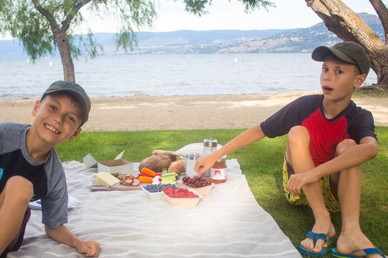 Two boys sitting next to a picnic by the beach