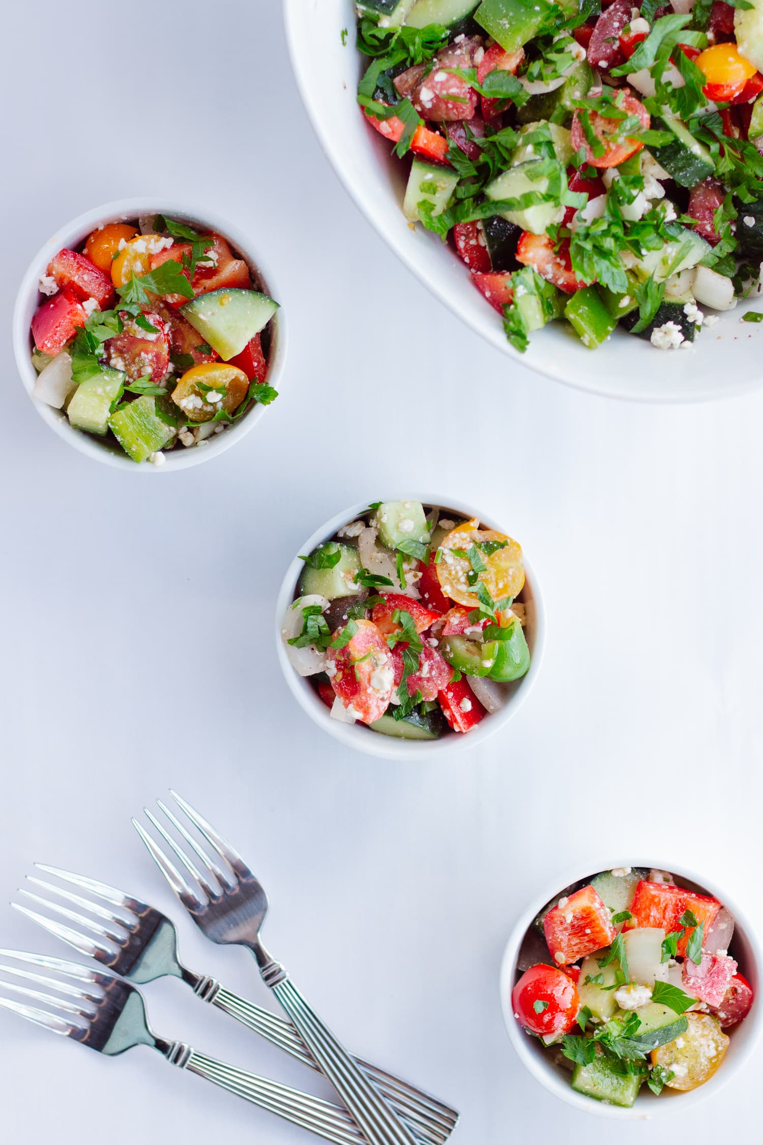 Overhead shot of chopped veggie salad in a large bowl and three small serving bowls with forks in the corner