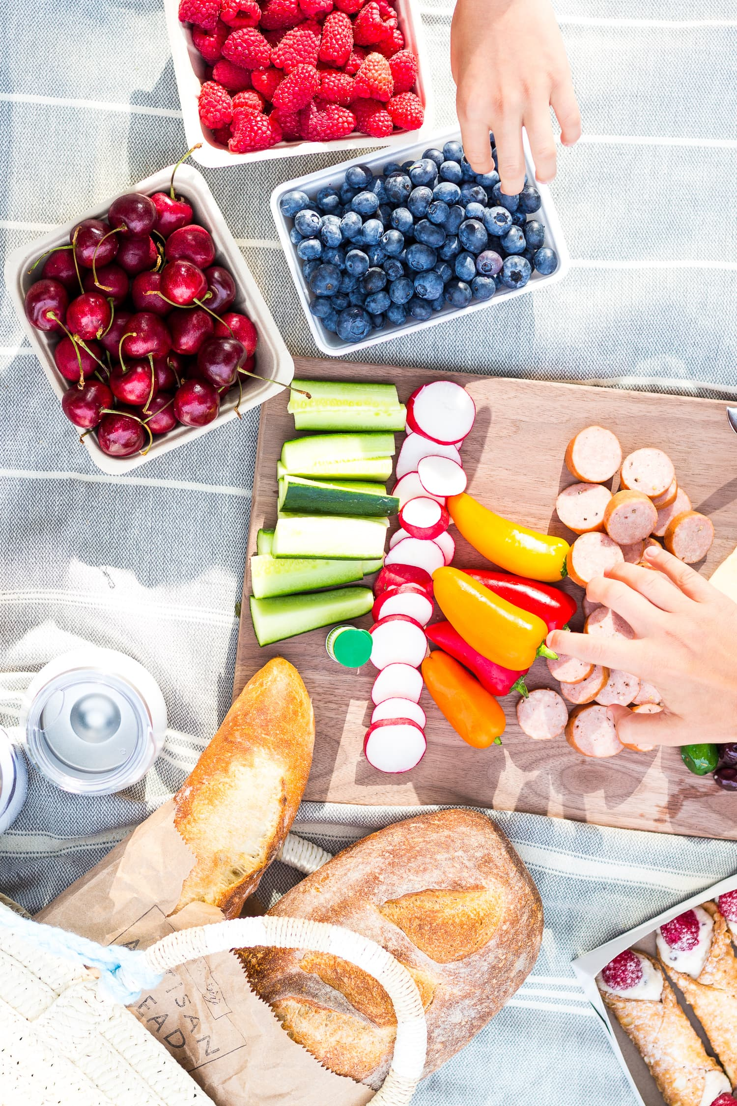 Overhead photo of a picnic set up on a blanket with two childrens hands reaching in.