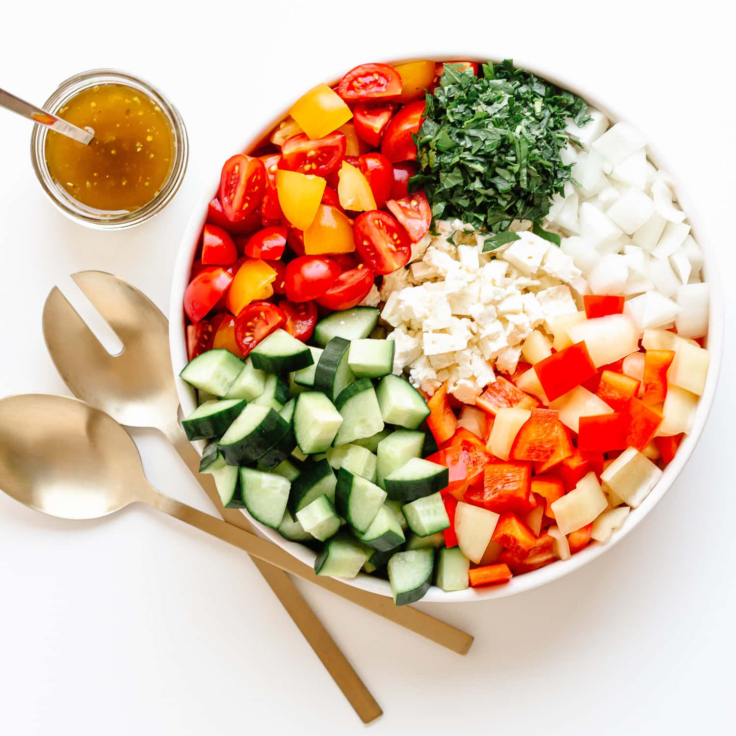 Variety of chopped veggies arranged separately in a bowl with dressing and salad servers on the side.