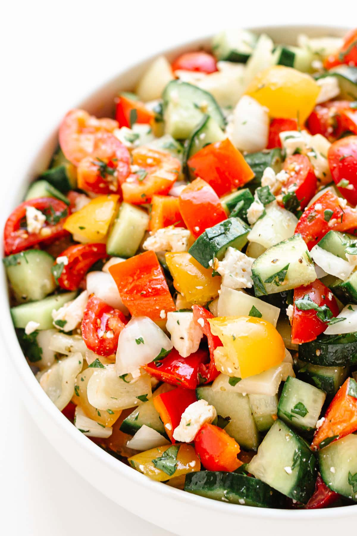 Bowl of Mediterranean style chopped salad on a white background.