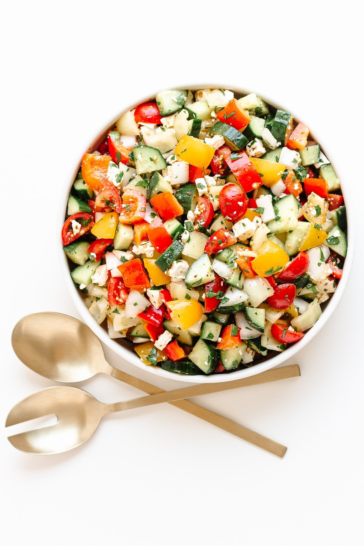 Bowl of summer chopped salad and gold salad servers on a white background.