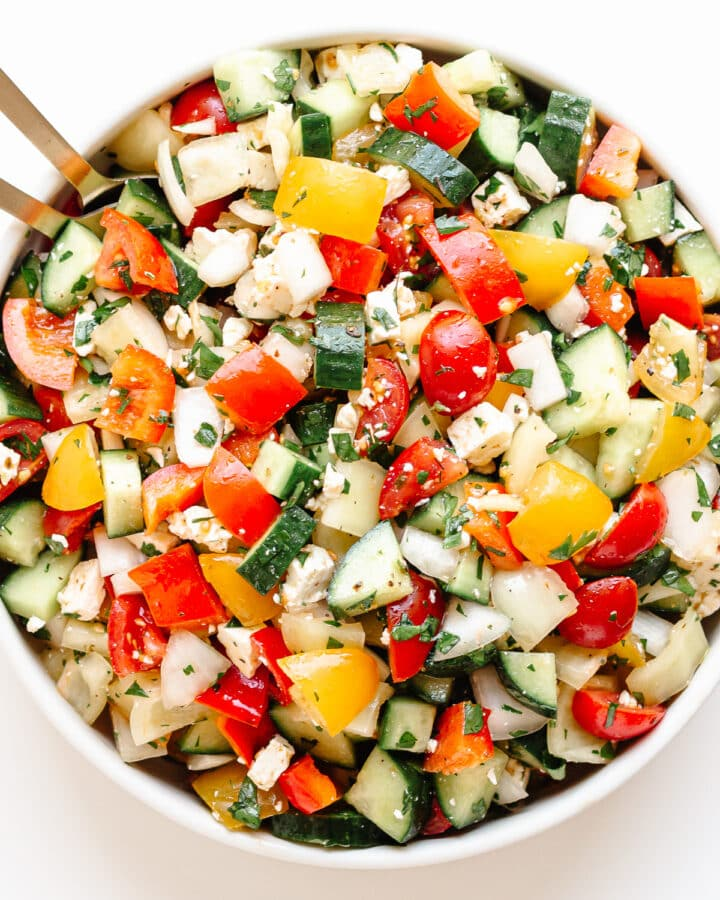 Bowl of chopped veggie salad with gold colored salad servers sticking out.