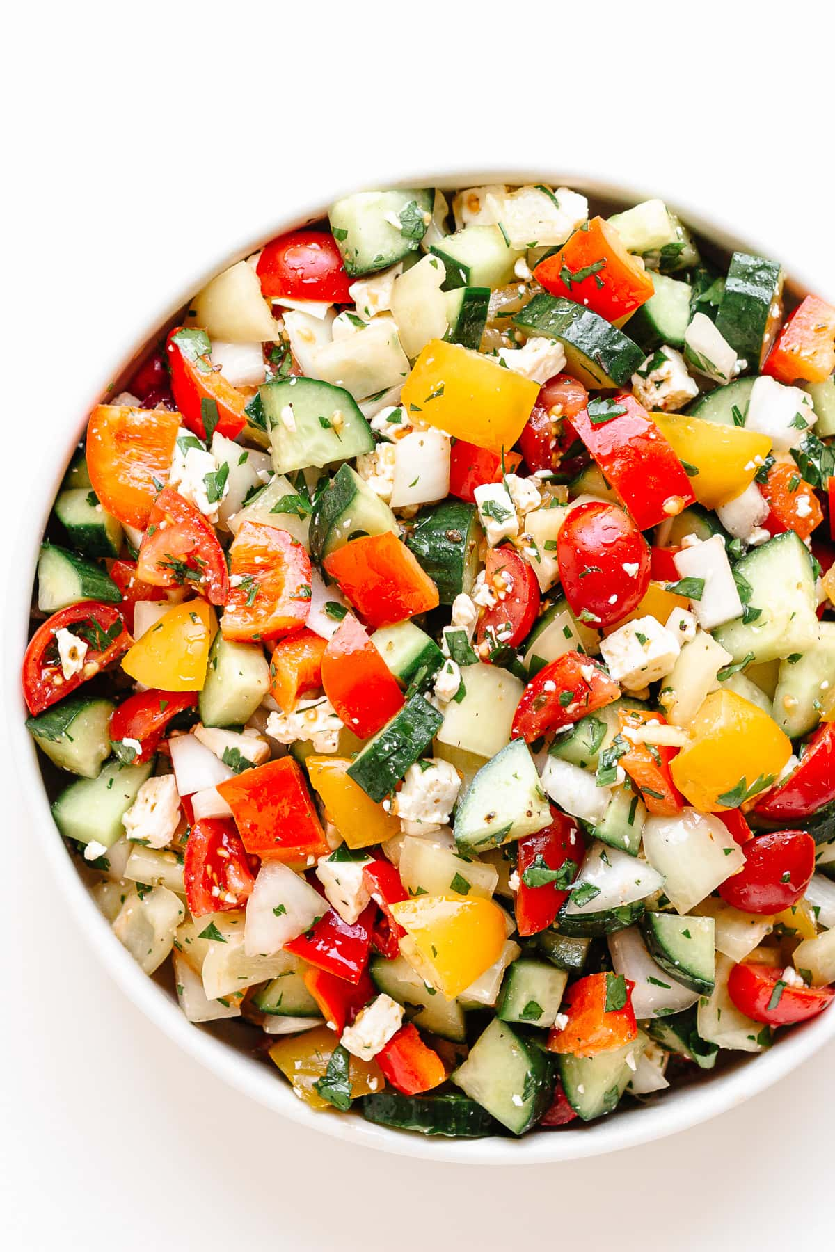 Close up of a bowl of summer chopped salad on a white background.