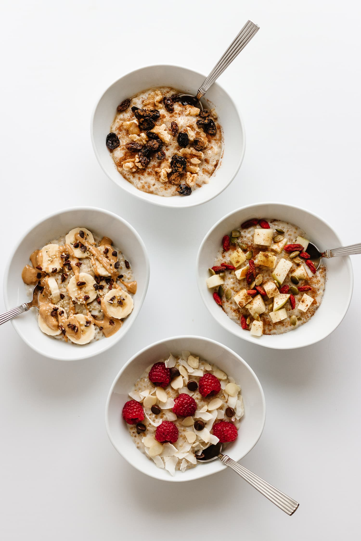 Four white bowls of steel cut oats with various toppings on a white background