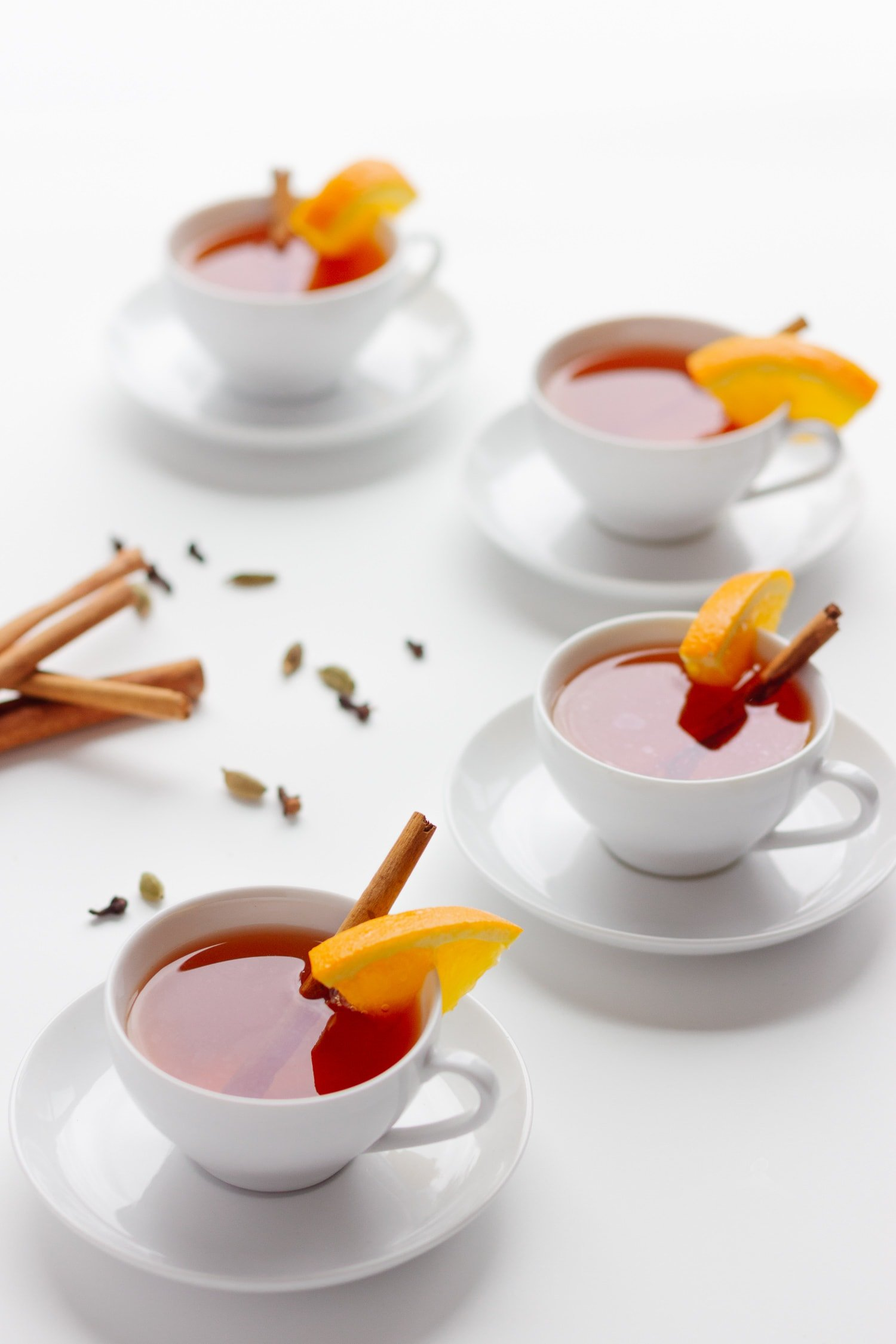 4 white tea cups arranged in a C pattern filled with Orange Spice Mulled Tea and decorated with an orange slice and cinnamon stick.