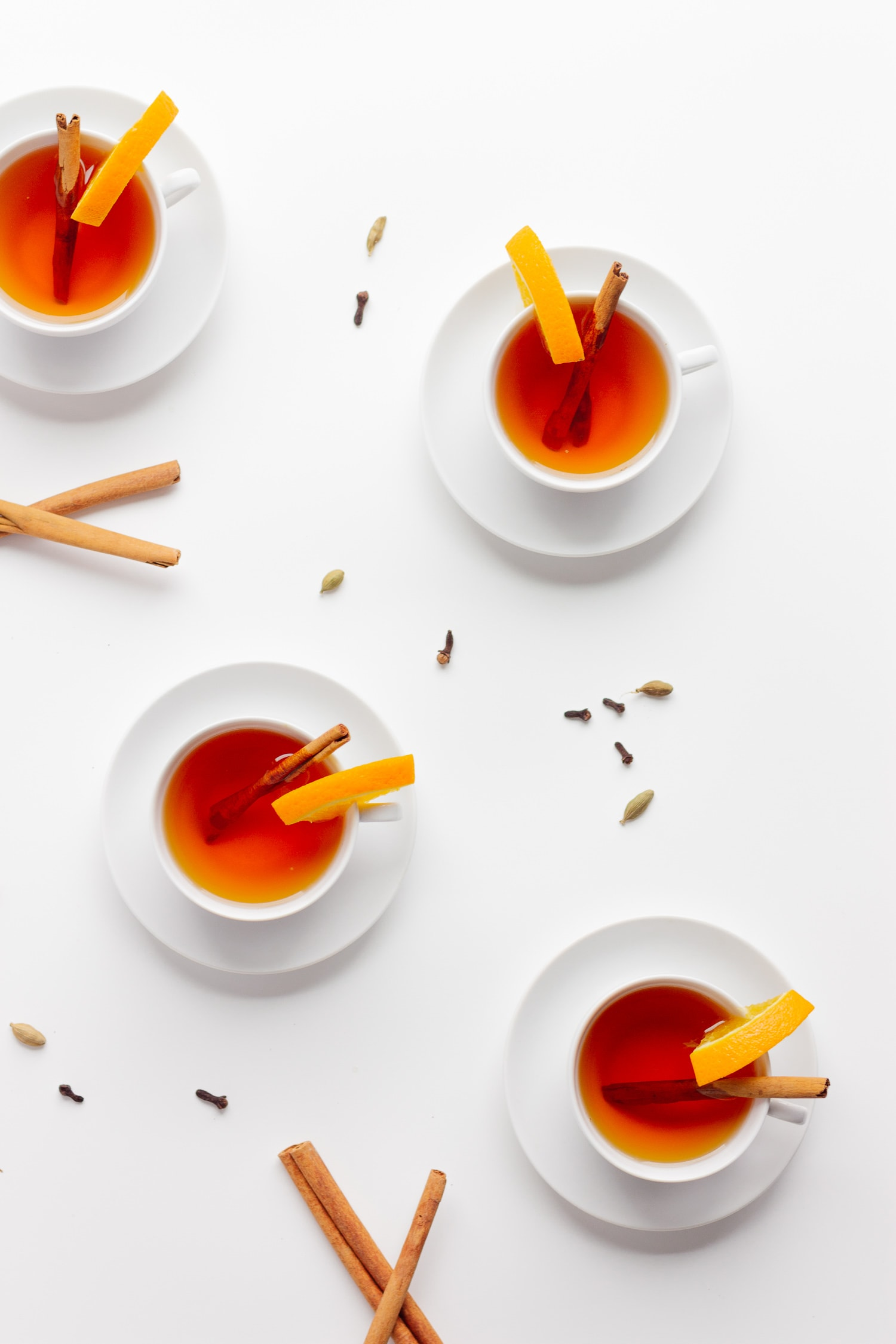 Overhead shot of 4 white tea cups filled with Orange Spice Mulled tea, decorated with an orange slice and cinnamon stick with cinnamon sticks, cloves and cardamom scattered around