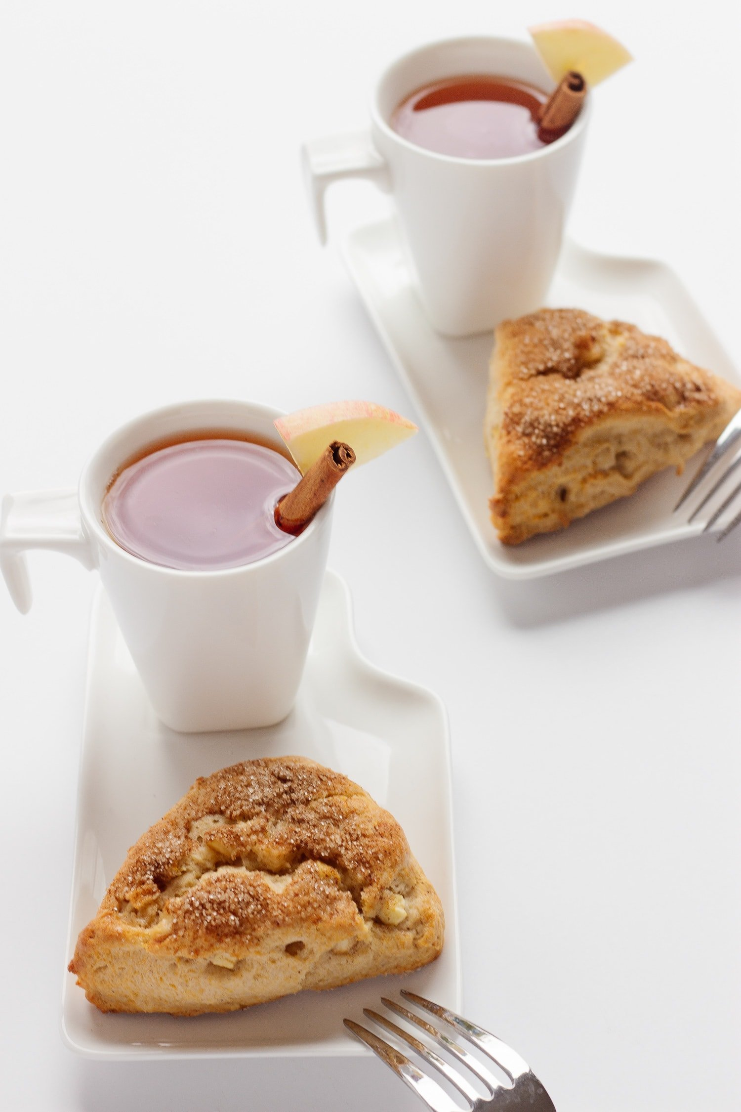Two white dessert plates each containing an apple cinnamon scone and cup of hot apple cider.