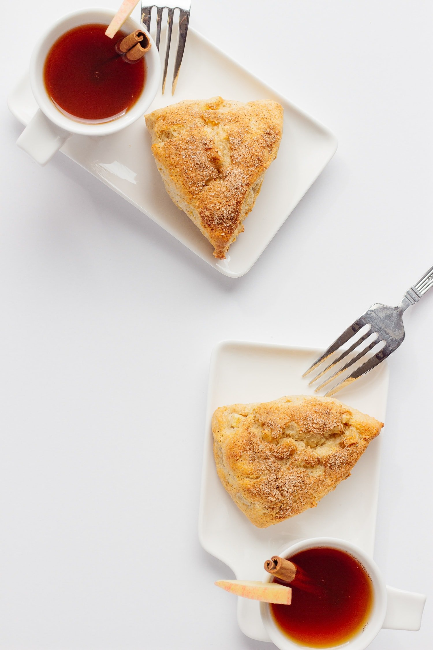 Two white dessert plates each holding an apple cinnamon scone and cup of hot apple cider with forks against the edge of the plate.