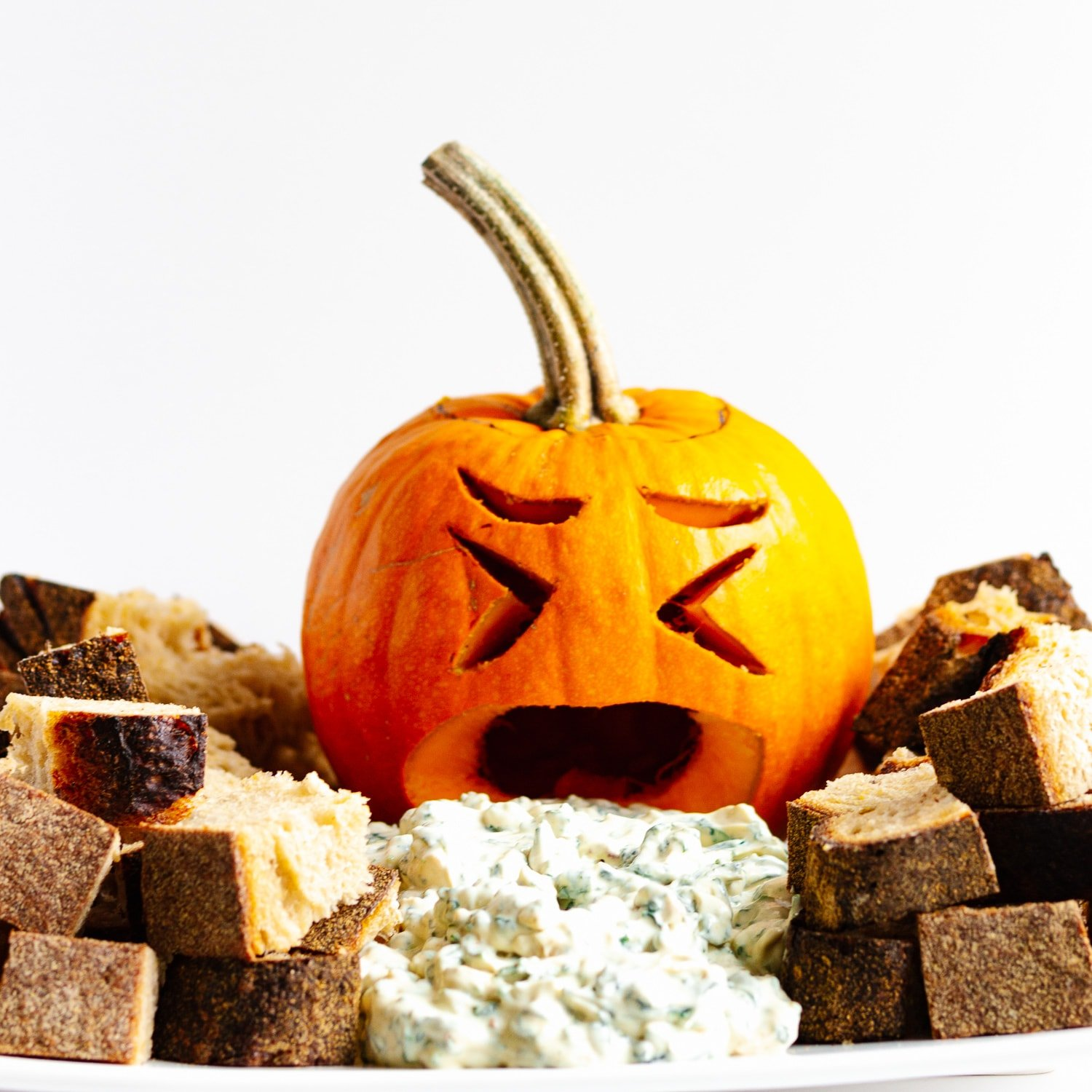 Small carved jack o' lantern with spinach dip pouring out of its mouth and surrounded by bread cubes.