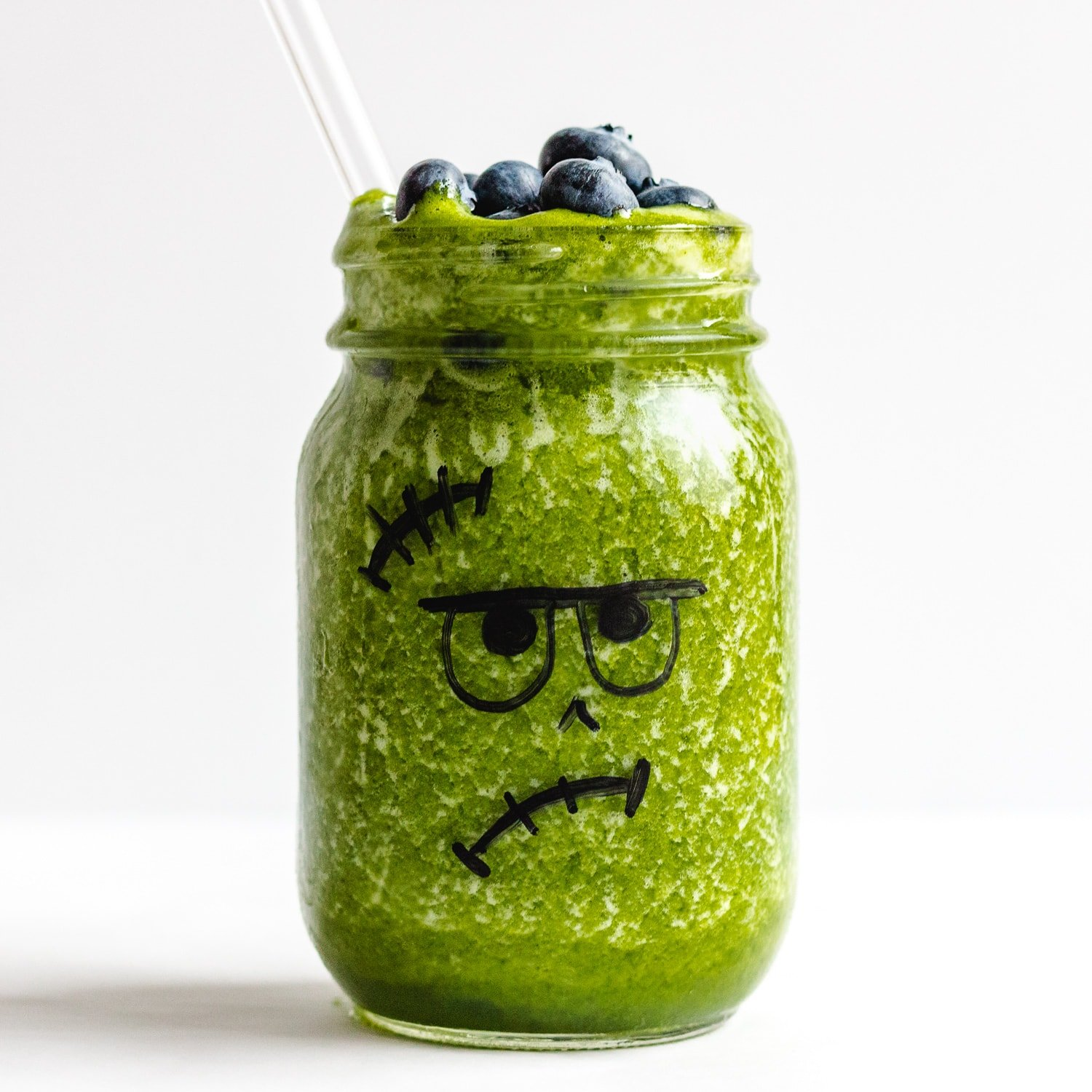 Frankenstein Green Smoothie - green smoothie poured into a jar that has a Frankenstein face drawn on and topped with blueberries