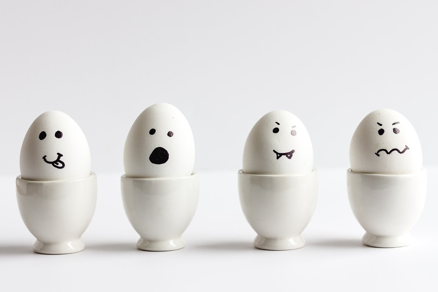 Four hardboiled eggs in white egg holders with faces drawn on to resemble Halloween ghosts.