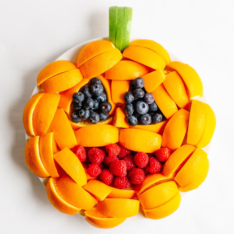 A fruit tray arranged to look like a jack o' lantern