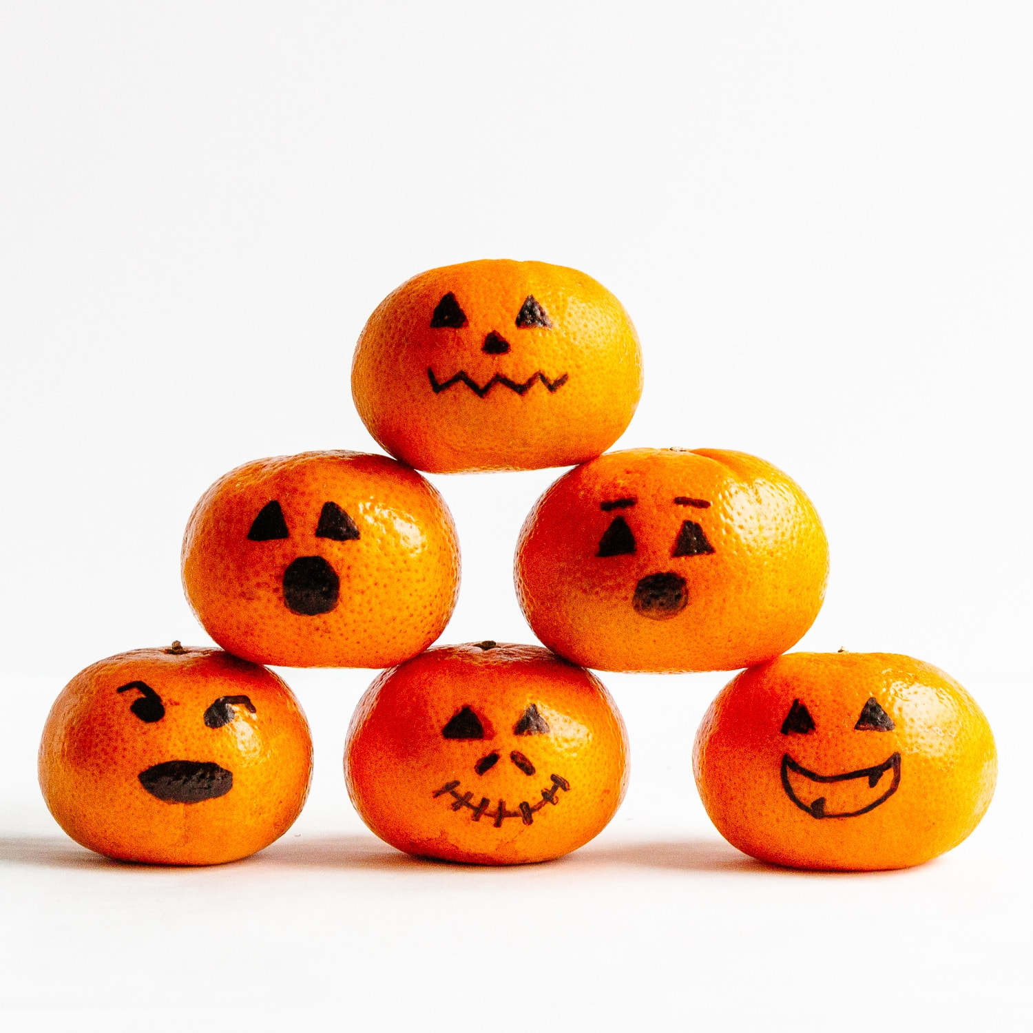 Mandarins with faces drawn on with black permanent marker to look like Jack O' Lanterns.