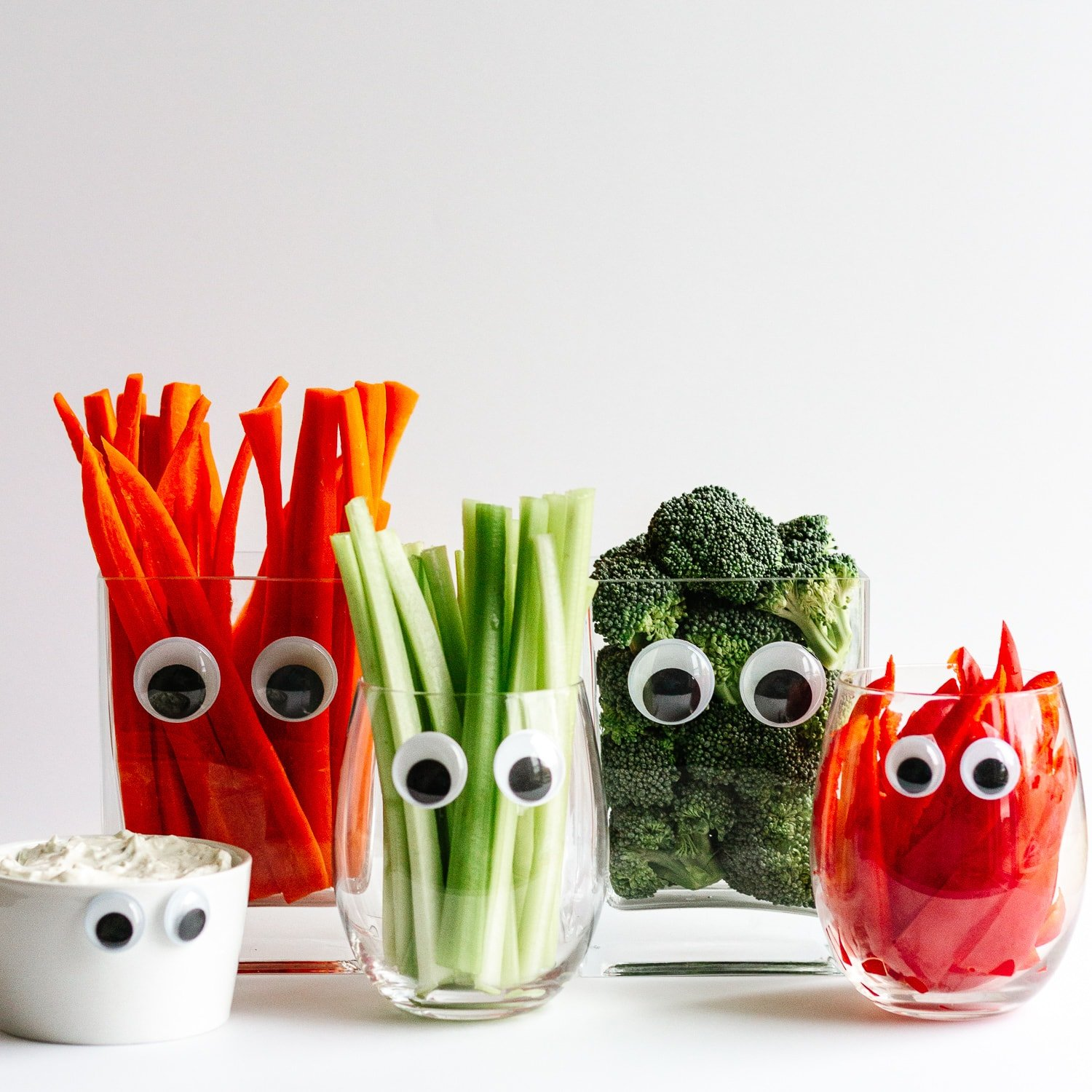 Monster Veggies and Dip: Variety of glasses with googly eyes filled with veggies and dip for a healthy Halloween themed snack