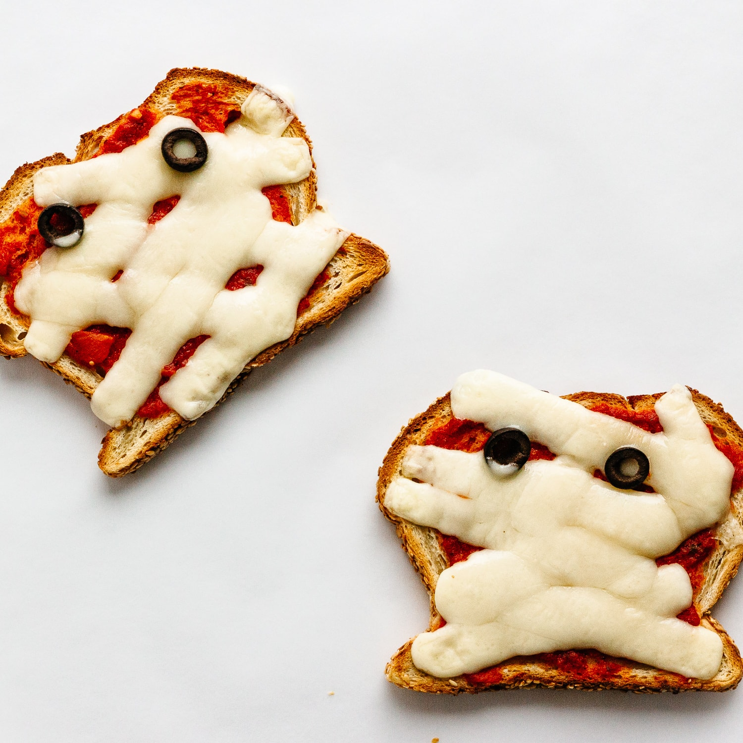 Pizza toast with strips of mozzarella and 2 black olive slices to look like a Halloween Mummy