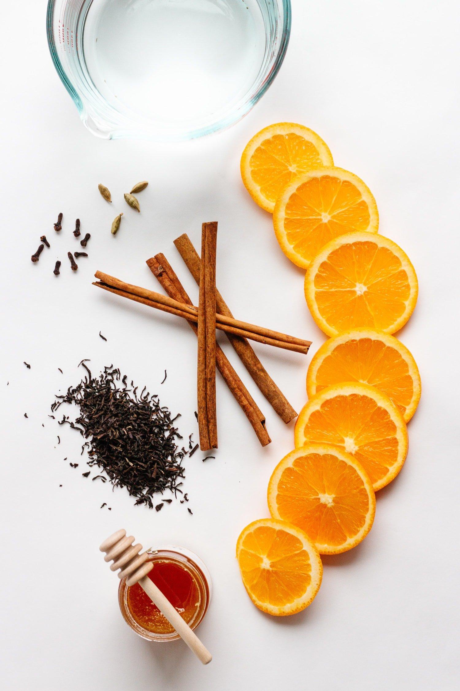 Overhead shot of ingredients for Orange Spice Mulled Tea: water, loose leaf black tea, orange slices, cinnamon sticks, cardamom pods, cloves
