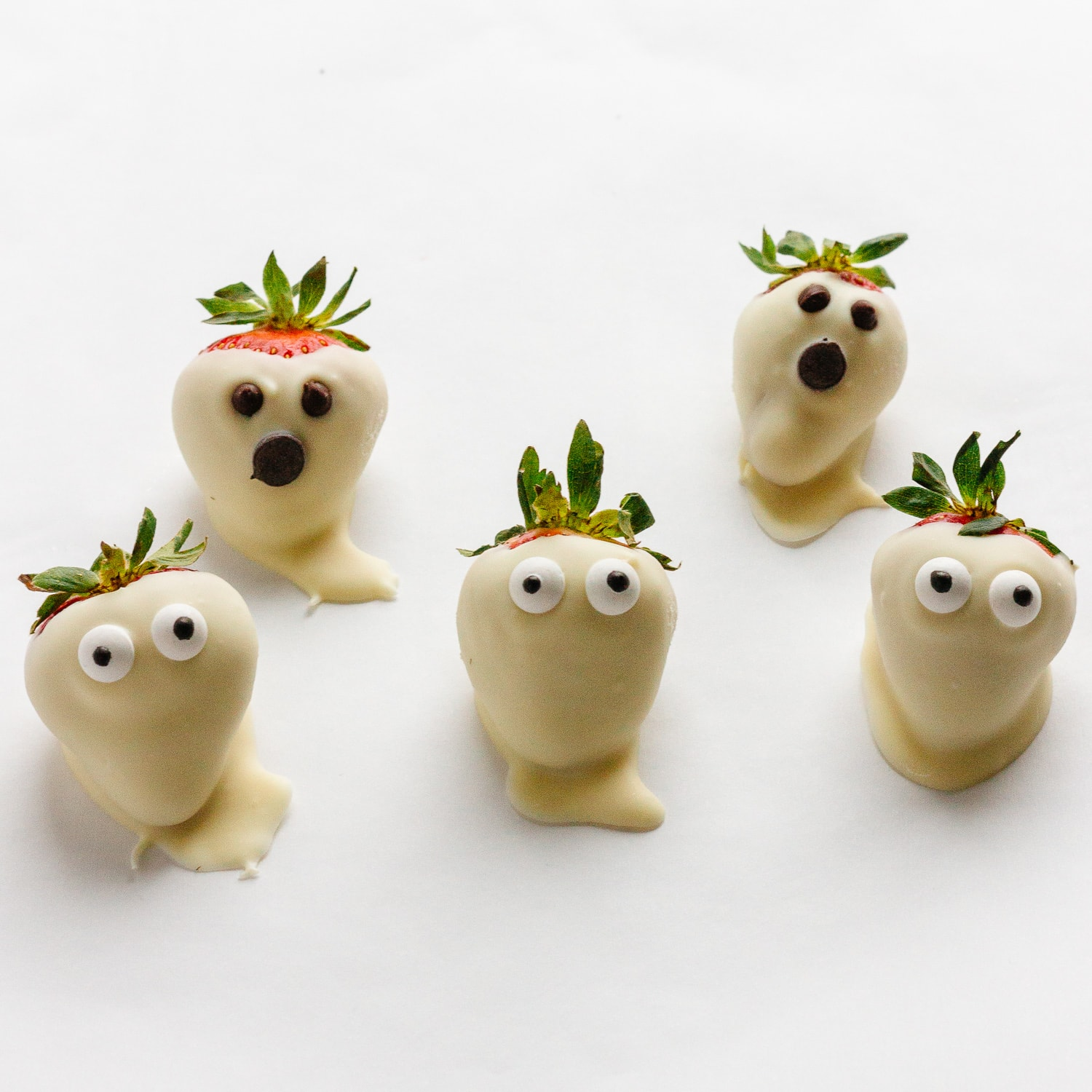 5 strawberry ghosts on a white surface.  Strawberries dipped in white chocolate with either candy eyeballs or chocolate chips.