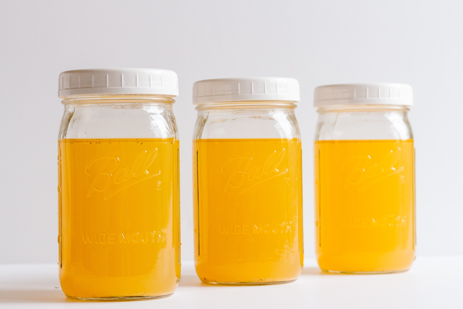 Three mason jars filled with golden coloured turkey stock