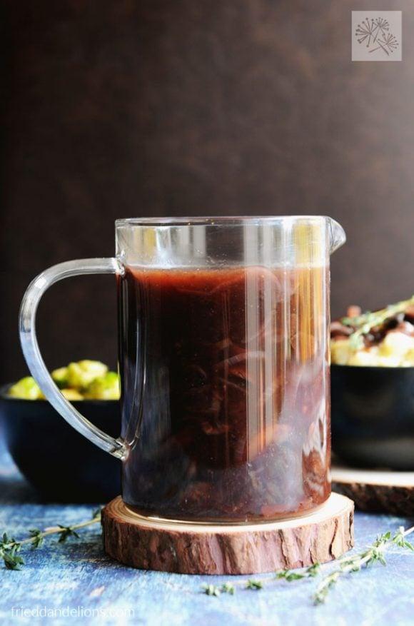 Vegan red wine gravy in a clear glass gravy pitcher set on a round wood slice