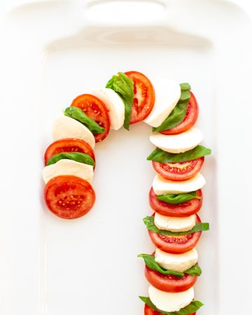 Caprese Salad arranged in the shape of a candy cane on a white platter