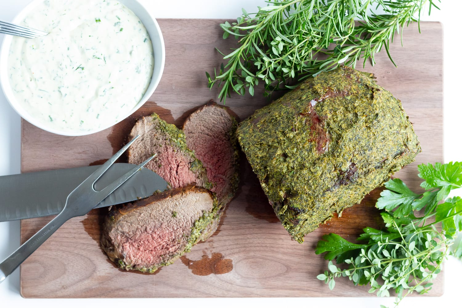 Overhead photo of herb mustard crusted roast beef on a wooden carving board with 3 slices carved off. There are also fresh herbs, bowl of creamy herb sauce and carving utensils laid out on the board.