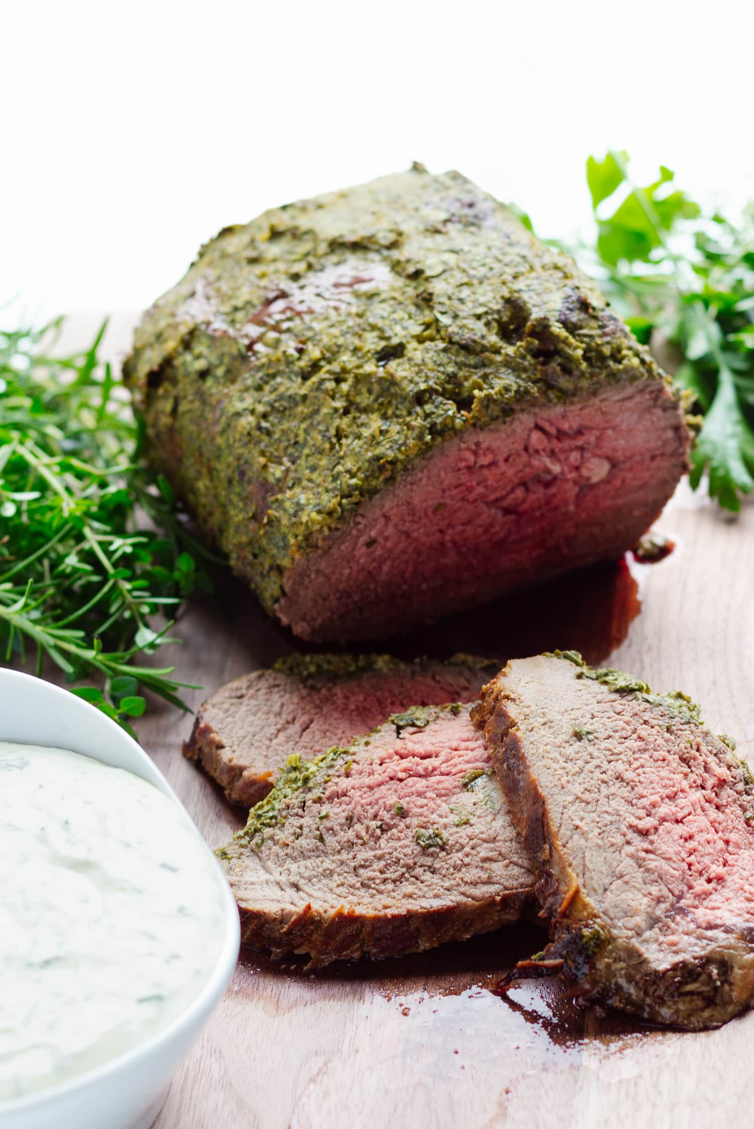 Herb Crusted Roast Beef on a wooden cutting board with 3 slices carved off in front. Also a bowl of creamy herb sauce and fresh herbs on the board.
